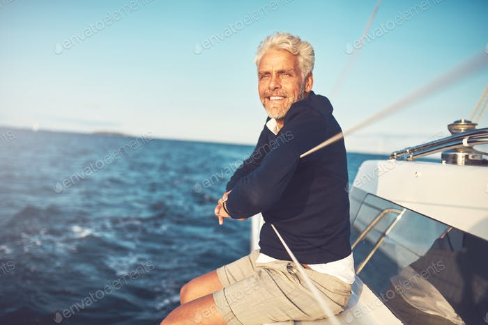 Smiling mature man admiring the sea view from his sailboat