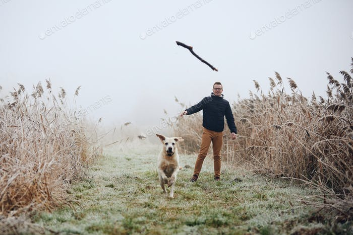Man throwing stick for his dog in autumn nature
