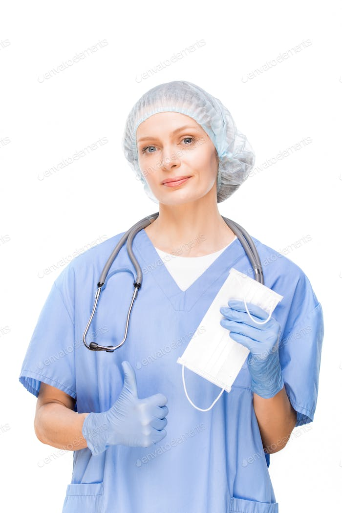 Young dentist, surgeon or other professional pointing at protective mask