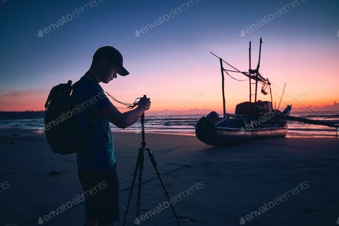 Photographer on beach at beautiful sunrise