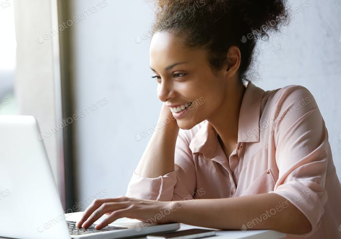 Beautiful young woman smiling and looking at laptop screen