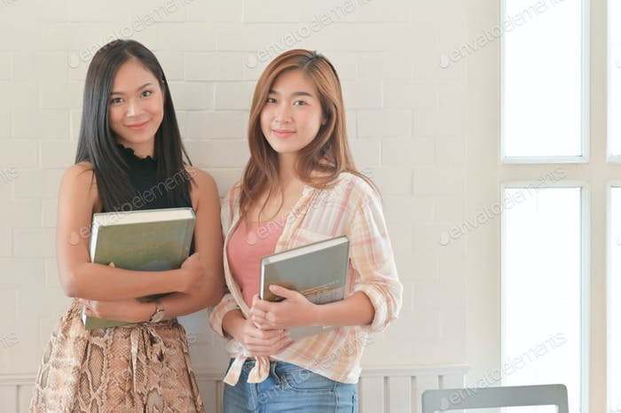 A portrait of a two Asian female students holding a book. They are preparing for university studies.