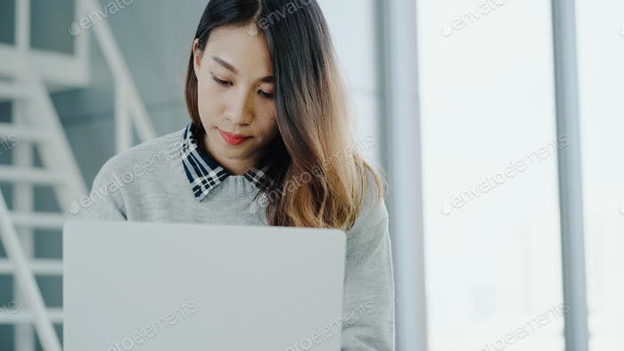 Young Asian female manager using portable computer device while sitting.