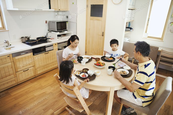 Family home. A family of two adults and two children seated at a meal at home.