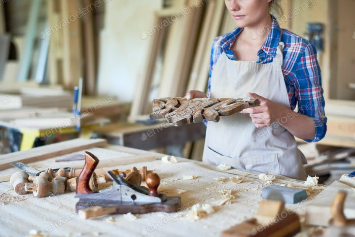 Female Carpenter Carving Wooden Part in Workshop
