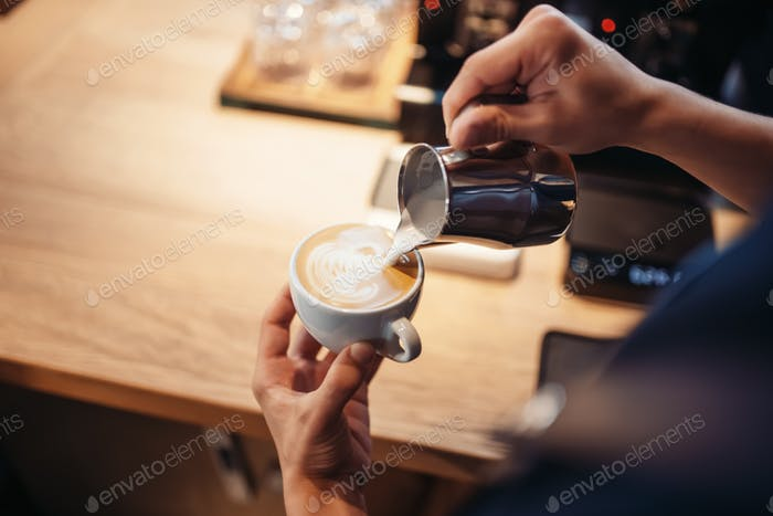 Barista hand pours cream into the cup of coffee