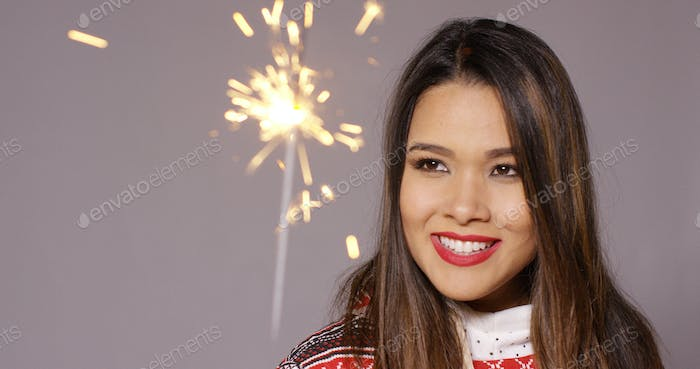 Attractive young woman celebrating with a sparkler