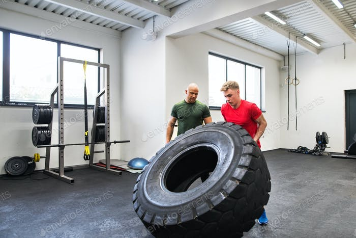 Fit young man with a personal trainer in gym working out, moving tire.
