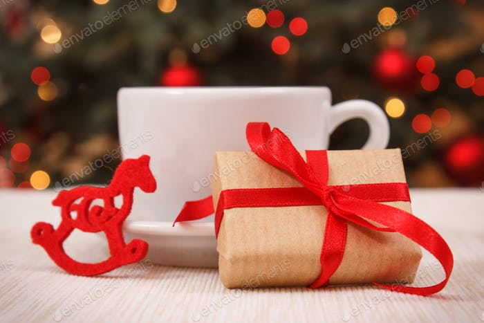Wrapped gift, cup of hot tea or coffee and christmas tree with lights