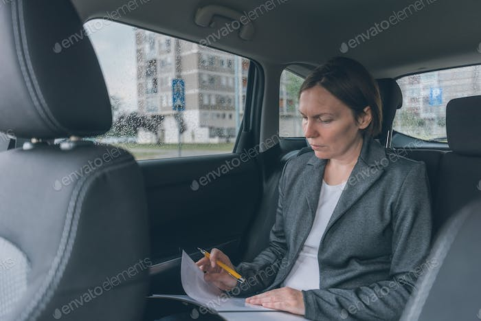 Businesswoman doing business paperwork on car back seat