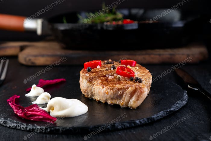 Grilled pork steak on slate plate.