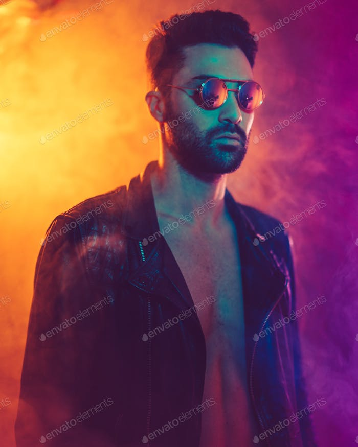 Cinematic portrait of Handsome man with sunglasses, smoke, leather jacket and color lights