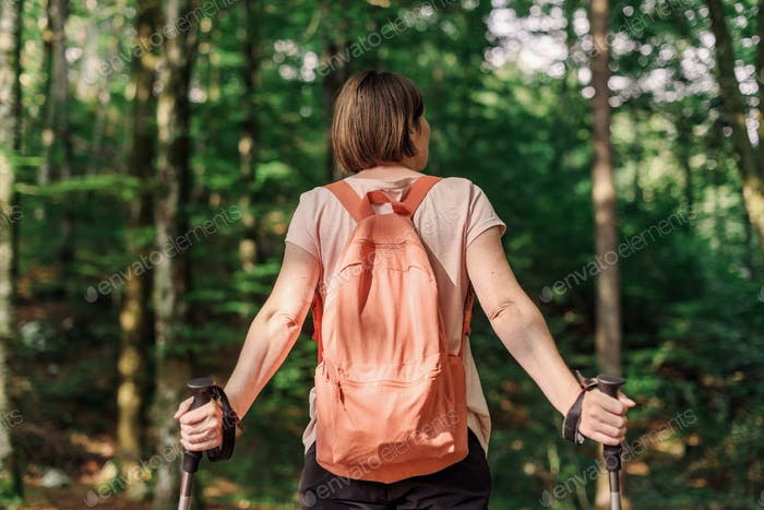 Female hiker with hiking poles resting in forest