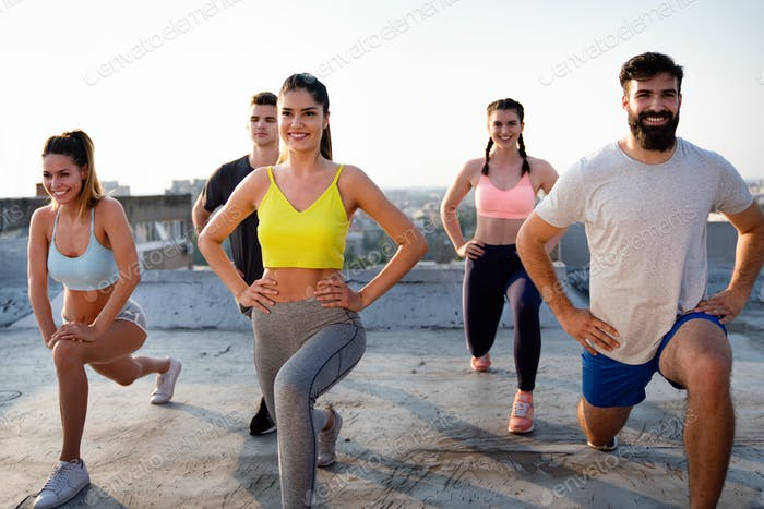 Group of happy fit people friends exercising together outdoor