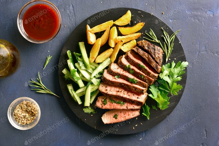 Beef steak with potato wedges and cucumber salad
