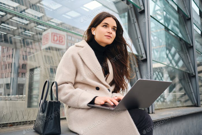 Thumbnail for Young pretty businesswoman dreamily working on laptop on street