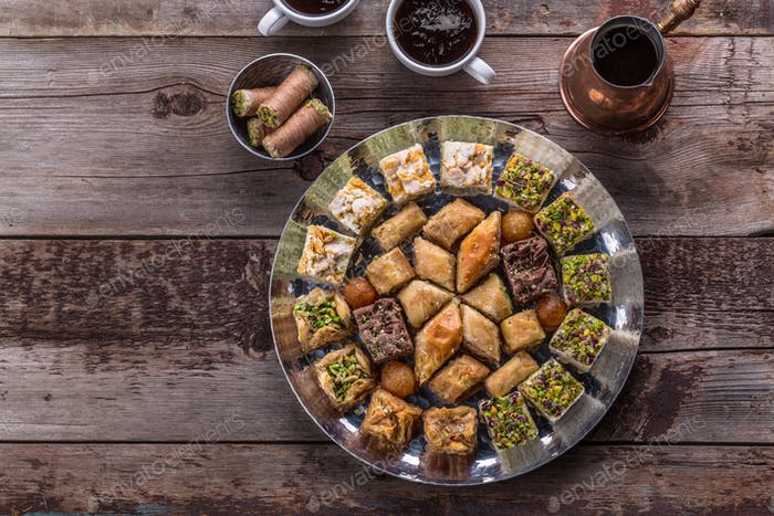 Traditional baklava and delights on a copper plate with coffee, copy space