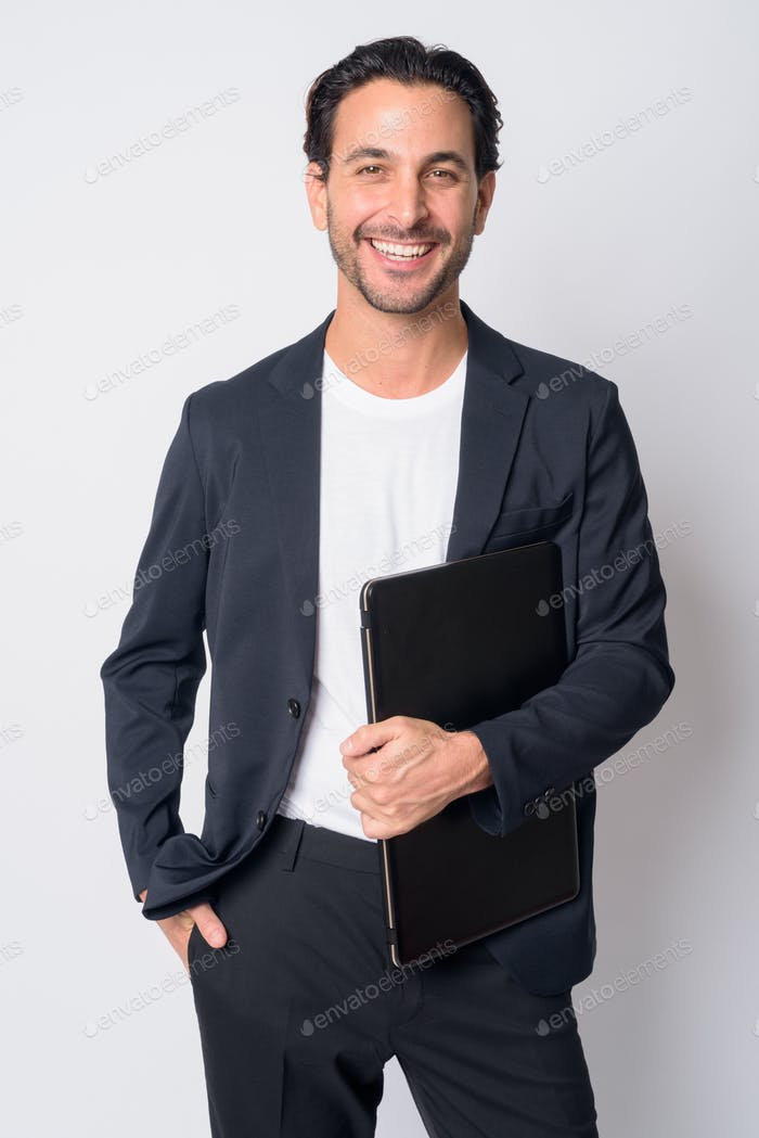 Portrait of happy handsome Hispanic businessman holding laptop