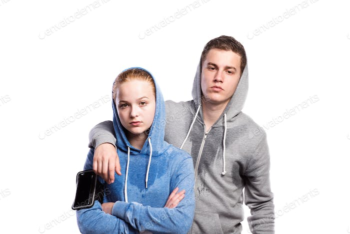 Teenage boy and girl in sweatshirts. Studio shot, isolated.