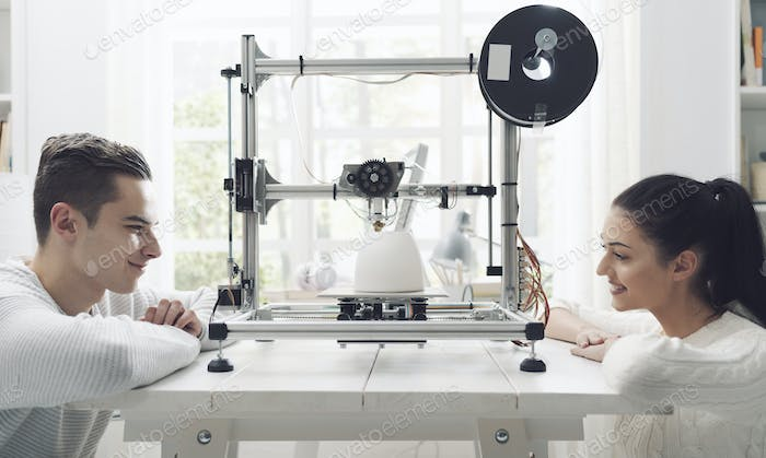 Engineering students using a 3D printer in the lab