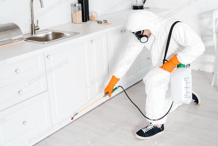 Kammerjäger hält giftige Geräte in der Nähe von Küchenschrank
