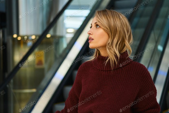 Beautiful blond girl in knitted sweater dreamily looking away on escalator in shopping mall