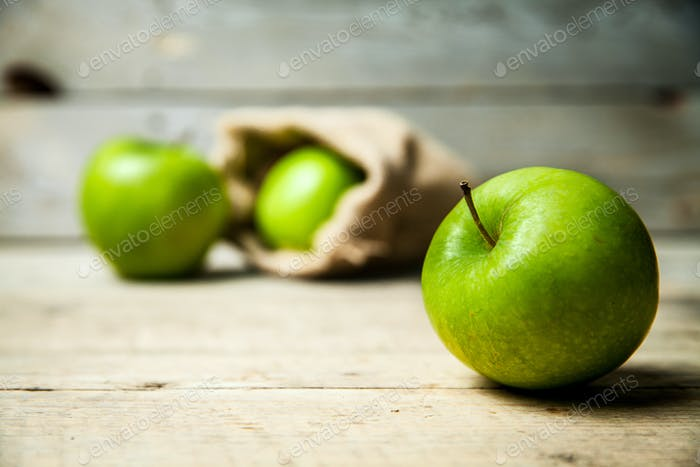 fruit. Ripe green apples with burlap, on wooden  backgroun
