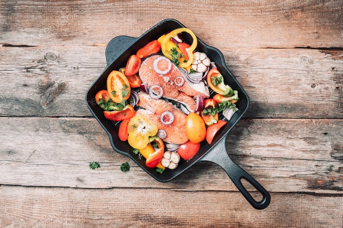 Healthy food. Dinner cooking ingredients. Raw uncooked salmon fish with vegetables, herbs, spices in
