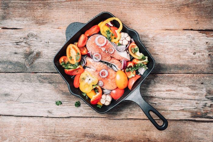Gesundes Essen. Abendessen Kochzutaten. Roher ungekochter Lachsfisch mit Gemüse, Kräutern, Gewürzen in