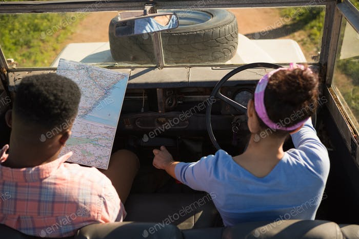 Couple looking at map while driving a car
