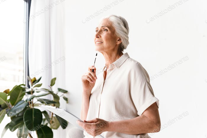 Thoughtful mature business woman taking notes