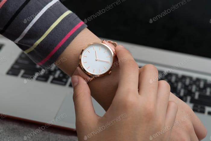 Girl's hand with wrist watch in front of desk with laptop computer