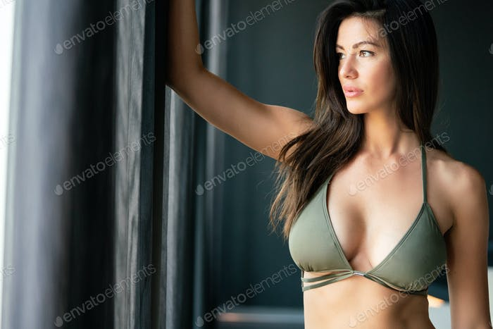 Sexy woman posing by the window in daylight