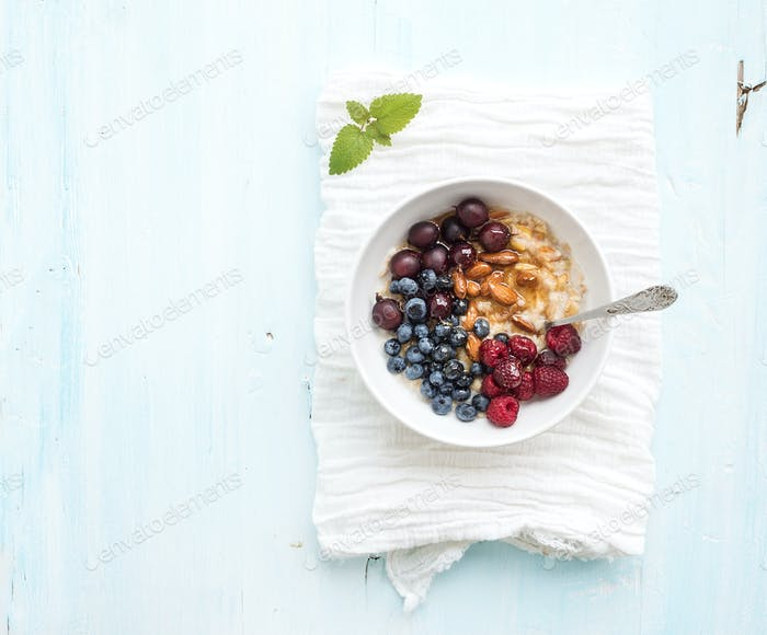 Healthy breakfast set. Bowl of oat porridge with fresh berries, almond and honey