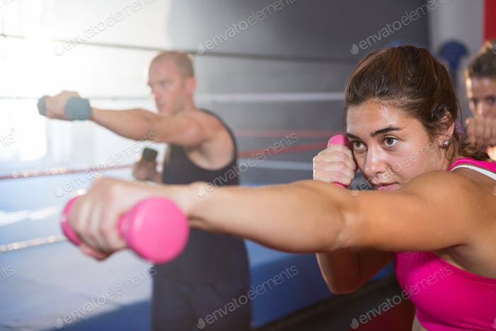Young female punching with dumbbell
