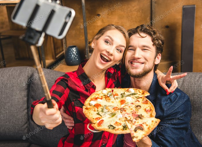 Happy couple taking selfie with pizza