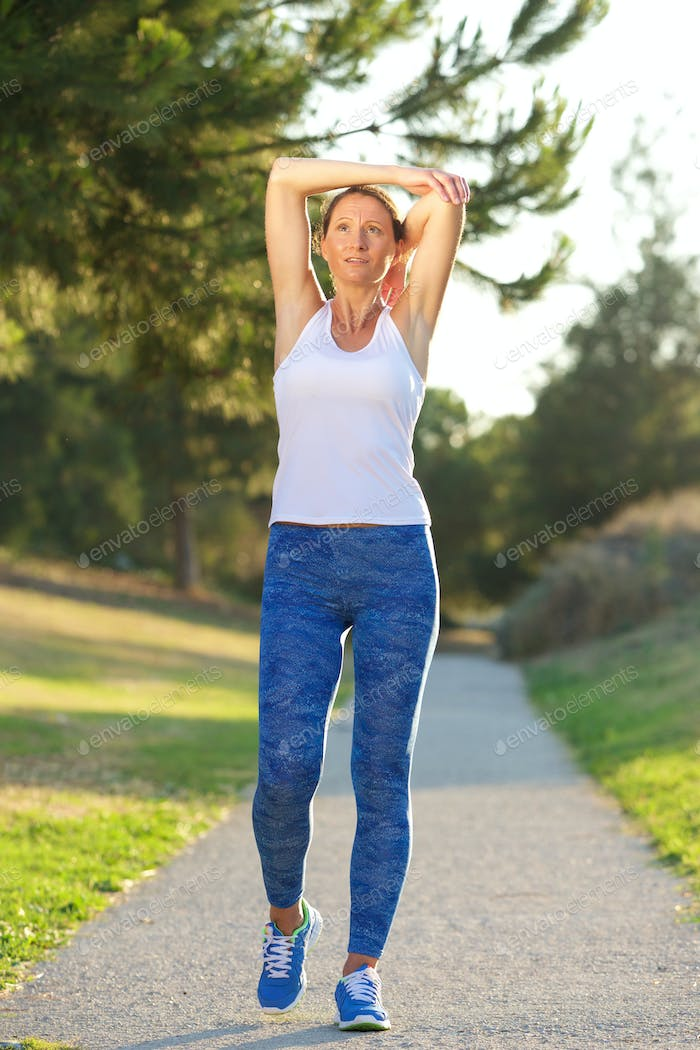 Healthy older woman stretching muscles after workout