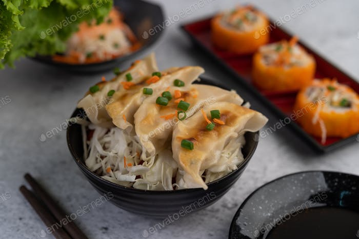 Gyoza in a black cup with a cup of sauce.
