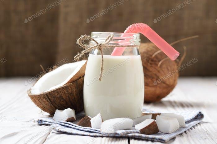 Mason Glas Milch oder Joghurt auf blaue Serviette auf weißem Holztisch