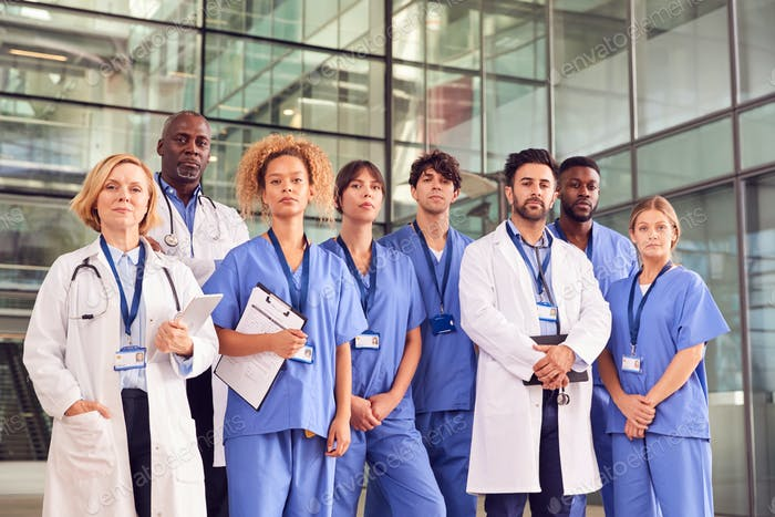 Portrait Of Serious Medical Team Standing In Modern Hospital Building