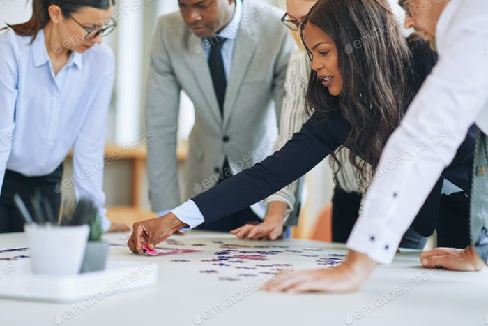 Diverse businesspeople standing in a boardroom solving a jigsaw puzzle