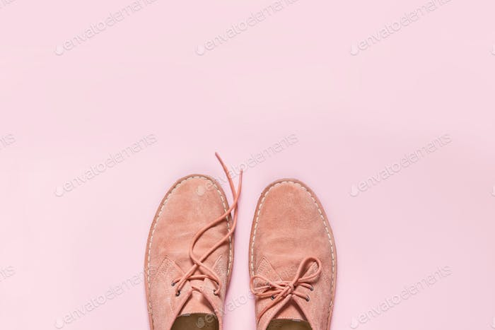 Orange suede shoes with pink background