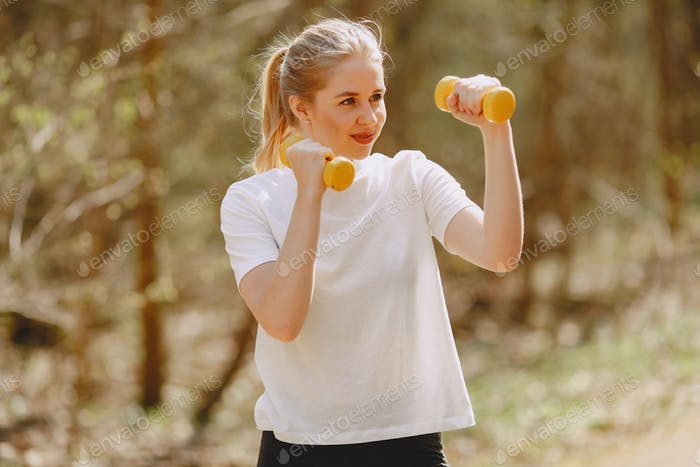 Sports girl training in a summer forest