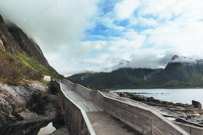 Boardwalk leading towards mountains against cloudy sky