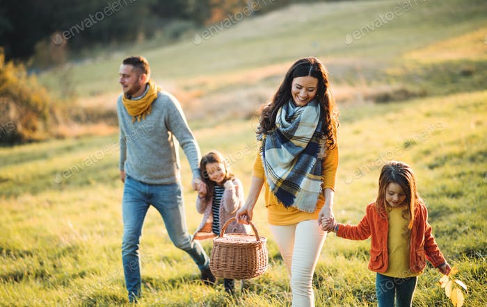 A young family with two small children walking in autumn nature