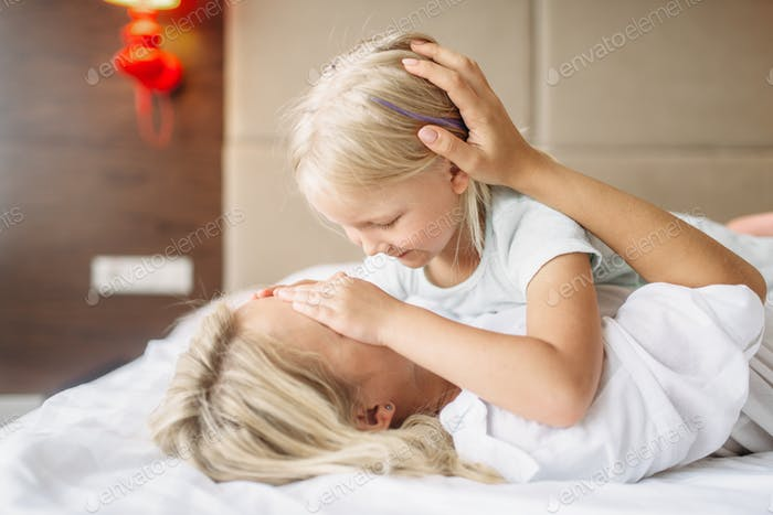 Cheeful mother and child plays lying on the bed