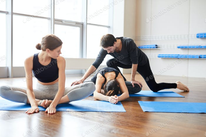 Yoga teacher correcting student at class