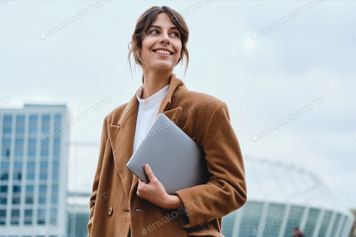 Young pretty smiling businesswoman in coat with laptop happily looking away on city street