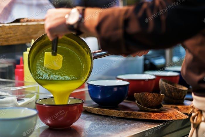 Man cooking tasty orange soup or sauce