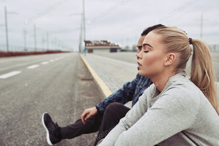 Young couple sitting on a curb after jogging together